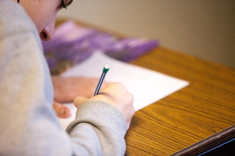 o-que-cai-no-enem - Descrição da imagem: estudante escrevendo com lápis em uma folha branca.