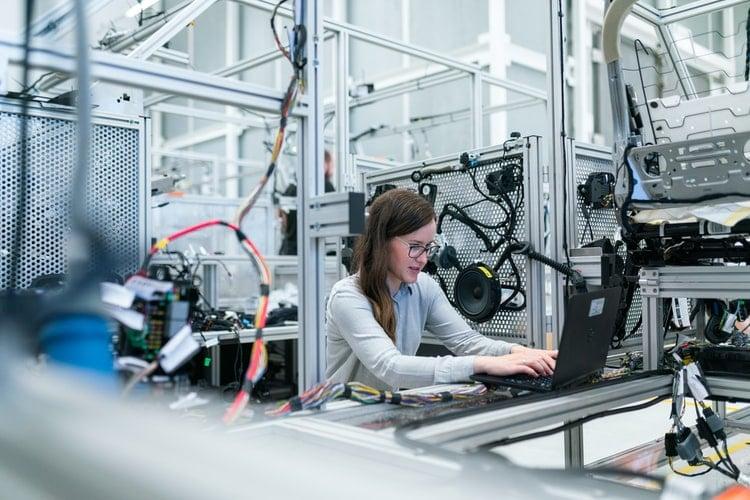 Mulher jovem, profissional de Engenharia de Produção, trabalhando em um computador numa indústria.