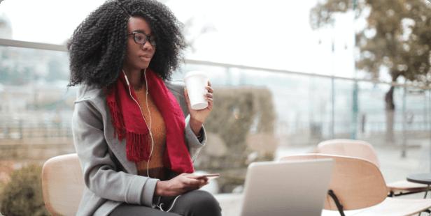 Aluna da graduação EAD sentada na frente de um notebook, usando um celular e fones de ouvido e segurando um copo de café.